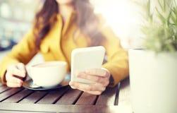 Ciérrese para arriba de la mujer que manda un SMS en smartphone en el café Fotografía de archivo
