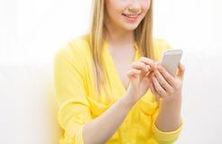 Ciérrese para arriba de la mujer que manda un SMS en smartphone en casa Imagenes de archivo