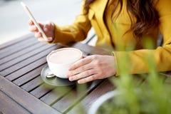 Ciérrese para arriba de la mujer que manda un SMS en smartphone en el café Imagen de archivo libre de regalías