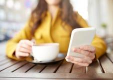 Ciérrese para arriba de la mujer que manda un SMS en smartphone en el café Fotos de archivo