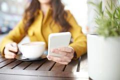 Ciérrese para arriba de la mujer que manda un SMS en smartphone en el café Fotos de archivo libres de regalías