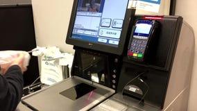 Ciérrese para arriba de la mujer que paga las comidas en el contador de la auto-comprobación almacen de metraje de vídeo