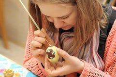 Ciérrese para arriba de la mujer que pinta los huevos de Pascua Fotos de archivo