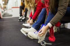 Ciérrese para arriba de la mujer que pone en patines de hielo Fotos de archivo libres de regalías