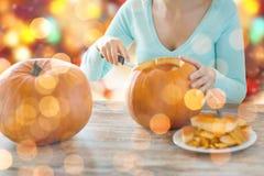 Ciérrese para arriba de la mujer que talla las calabazas para Halloween Fotos de archivo libres de regalías