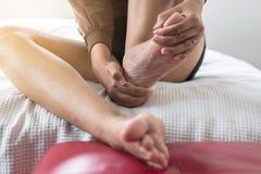 Ciérrese para arriba de la mujer que tiene un único dolor del talón o del pie, sensación femenina agotada y dolorosa foto de archivo libre de regalías
