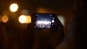 Ciérrese para arriba de la mujer que toma las fotos de fuegos artificiales en su smartphone metrajes