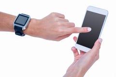 Ciérrese para arriba de la mujer que usa su smartphone y llevando el smartwatch Imagen de archivo