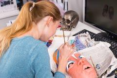 Ciérrese para arriba de la mujer rubia joven que pinta a Clay Mask Fotos de archivo libres de regalías