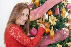 Ciérrese para arriba de la mujer sonriente hermosa que lleva una blusa roja delante de un christmast de adornamiento, feliz del á Foto de archivo libre de regalías