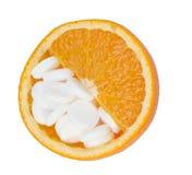 Ciérrese para arriba de la naranja y de las píldoras aisladas - concepto de la vitamina Imágenes de archivo libres de regalías
