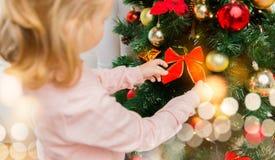 Ciérrese para arriba de la niña que adorna el árbol de navidad Imagenes de archivo