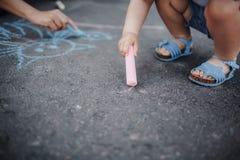 Ciérrese para arriba de la niña que dibuja con tizas en la acera fotografía de archivo libre de regalías