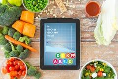 Ciérrese para arriba de la PC de la tableta con la carta y las verduras Imagen de archivo libre de regalías