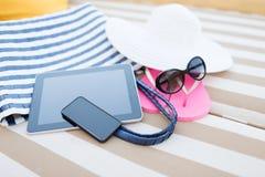 Ciérrese para arriba de la PC y del smartphone de la tableta en la playa Imagenes de archivo