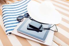 Ciérrese para arriba de la PC y del smartphone de la tableta en la playa Fotografía de archivo