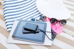 Ciérrese para arriba de la PC y del smartphone de la tableta en la playa Fotos de archivo libres de regalías