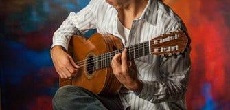 Ciérrese para arriba de la persona que toca la guitarra acústica imagen de archivo