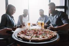 Ciérrese para arriba de la pizza en la tabla con los amigos de la compañía fotografía de archivo