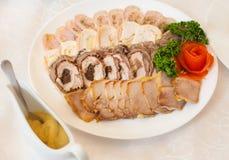 Ciérrese para arriba de la placa blanca por completo de los aperitivos de la carne adornados con r Imagen de archivo
