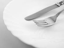 Ciérrese para arriba de la placa con la fork y el cuchillo Foto de archivo