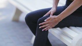 Ciérrese para arriba de la rodilla conmovedora en dolor, mujer del corredor del atleta de sexo femenino de la aptitud que corre e metrajes