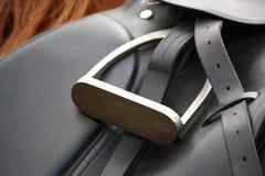 Ciérrese para arriba de la silla de montar negra en la parte posterior del caballo Foto de archivo libre de regalías