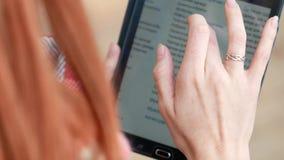 Ciérrese para arriba de la tableta, aplicaciones de la muchacha al aire libre almacen de metraje de vídeo