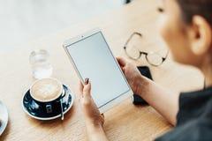 Ciérrese para arriba de la tableta morena joven de la tenencia de la mujer con la pantalla en blanco fotografía de archivo