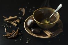 Ciérrese para arriba de la taza de cerámica marrón con el té verde caliente, pan de jengibre co fotos de archivo libres de regalías