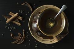 Ciérrese para arriba de la taza de cerámica marrón con té verde caliente con gingerbrea foto de archivo