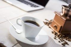Ciérrese para arriba de la taza de café en la tabla con la amoladora y un ordenador portátil Fotos de archivo