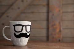 Ciérrese para arriba de la taza del café con leche con el bigote y las lentes en la tabla Imagen de archivo libre de regalías