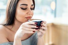 Ciérrese para arriba de la taza hermosa joven de la tenencia de la mujer de café y de disfrutar de su aroma fotos de archivo
