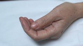 Ciérrese para arriba de la vieja mano femenina con las medicinas, tratamiento en la edad mayor, salud almacen de metraje de vídeo