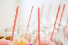 Ciérrese para arriba de las botellas de cristal para las bebidas con la paja Fotografía de archivo libre de regalías
