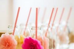 Ciérrese para arriba de las botellas de cristal para las bebidas con la paja Fotografía de archivo