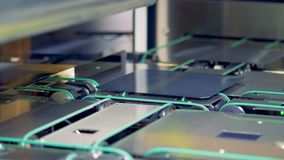 Ciérrese para arriba de las células solares del módulo que se mueven a lo largo del transportador en un equipo industrial moderno almacen de video