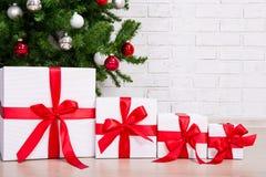 Ciérrese para arriba de las cajas de regalo debajo del árbol de navidad adornado Foto de archivo