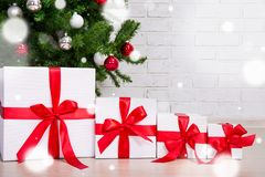 Ciérrese para arriba de las cajas de regalo debajo del árbol de navidad adornado con nieve Fotografía de archivo