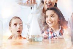 Ciérrese para arriba de las colegialas emocionales que miran su experimento que conduce del profesor Imagenes de archivo