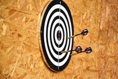 Ciérrese para arriba de las flechas de los dardos que son pegadas en el tablero de la blanco Fotos de archivo