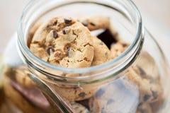 Ciérrese para arriba de las galletas de harina de avena del chocolate en el tarro de cristal Imagenes de archivo