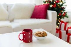 Ciérrese para arriba de las galletas de la Navidad y de la taza roja en la tabla Fotografía de archivo