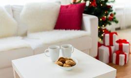 Ciérrese para arriba de las galletas y de las tazas de la Navidad en la tabla Imagen de archivo