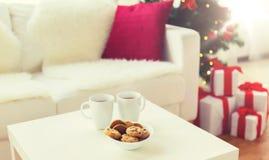 Ciérrese para arriba de las galletas y de las tazas de la Navidad en la tabla Imágenes de archivo libres de regalías