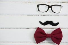 Ciérrese para arriba de las lentes y de la corbata de lazo dispuestas con el bigote en la tabla Foto de archivo libre de regalías