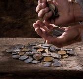Ciérrese para arriba de las manos caucásicas y de la pila del viejo hombre de monedas viejas Imagen de archivo