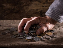 Ciérrese para arriba de las manos caucásicas y de la pila del viejo hombre de monedas viejas Foto de archivo