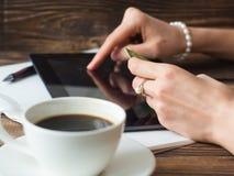 Ciérrese para arriba de las manos de la empresaria que hacen compras en línea con la tableta digital imagen de archivo libre de regalías